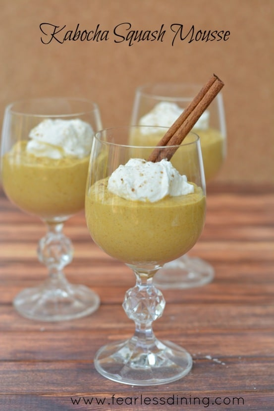 Kabocha Squash Mousse in three wine glasses. Whipped cream is on top of the mousse.