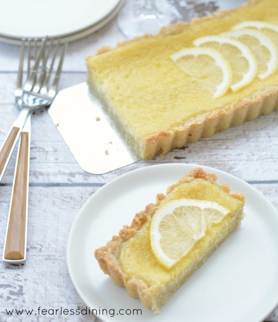 Gluten Free Lemon Tart on a table. A slice is on a plate and two forks are next to the plate