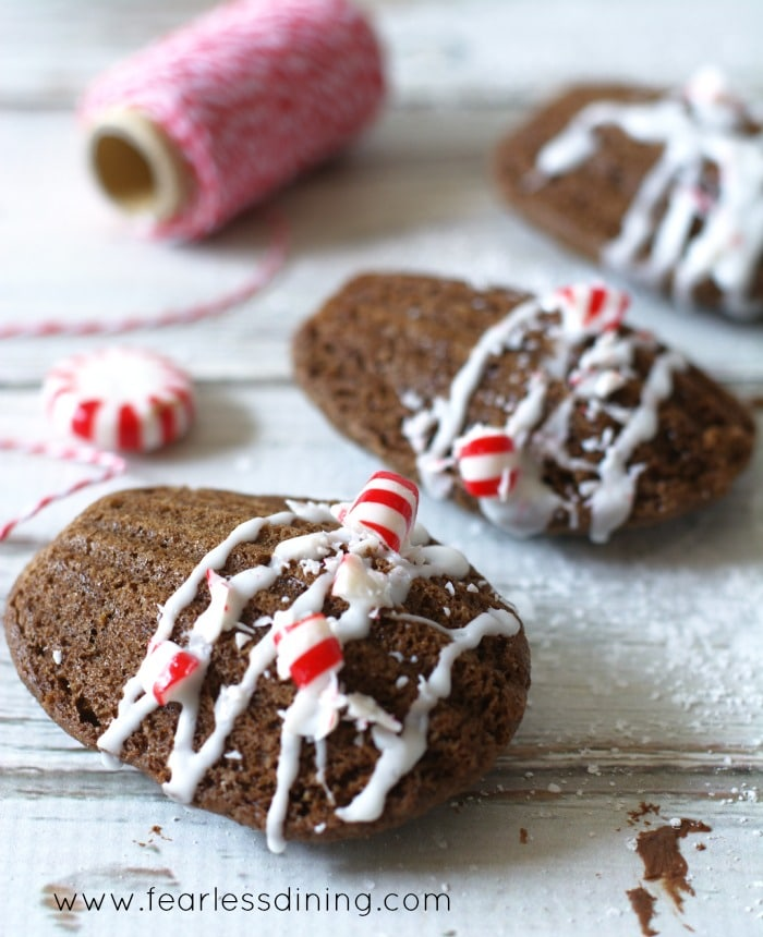 Gluten free Chocolate Mint Madeleines in a row. Each is topped with crushed peppermint candy