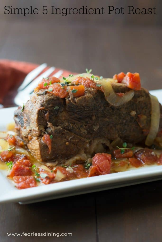 Quick and Easy 5 Ingredient Slow Cooker Pot Roast on a platter with onion and tomatoes on top