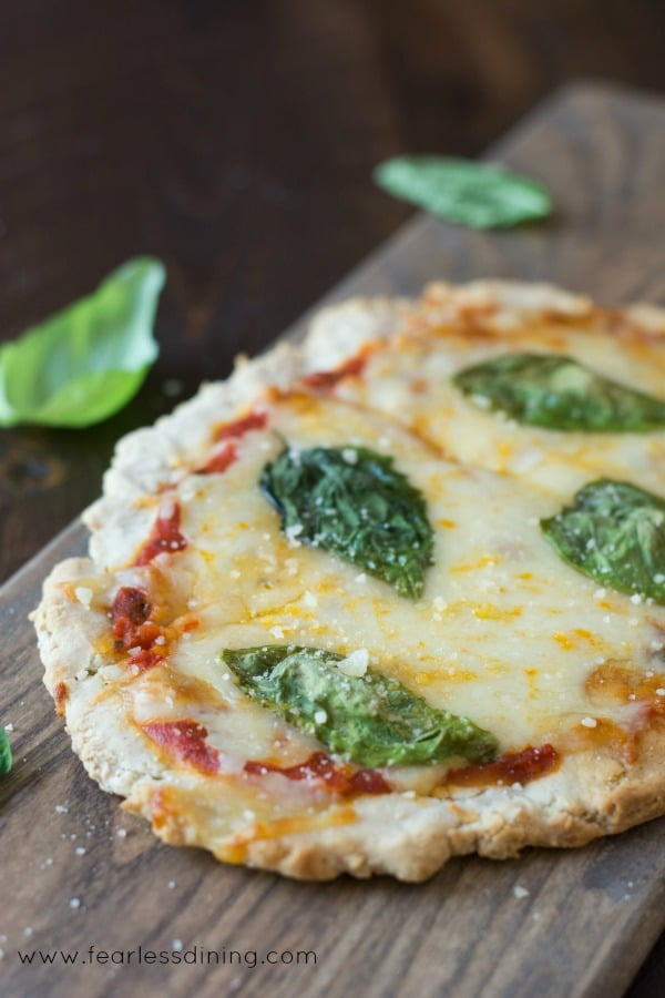 Gluten Free Flatbread Tomato Basil Pizza on a cutting board with fresh basil leaves.