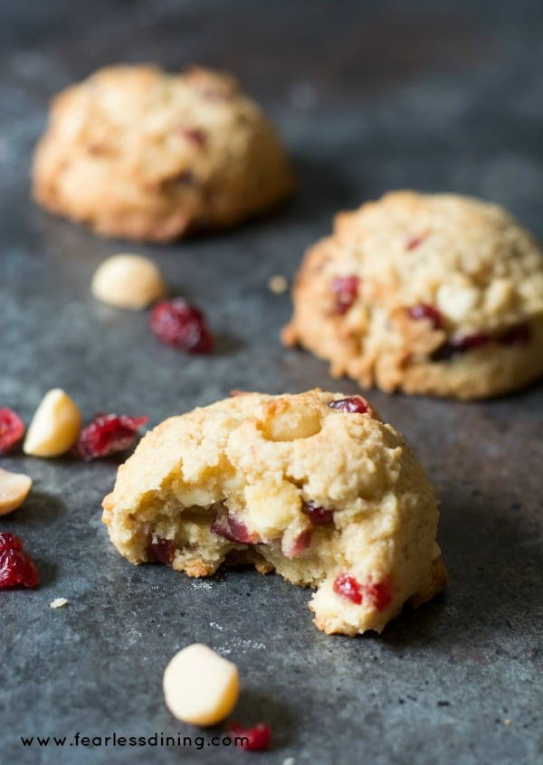 Gluten Free Cranberry White Chocolate Chip Cookies on a cookie sheet with macadamia nuts and cranberries