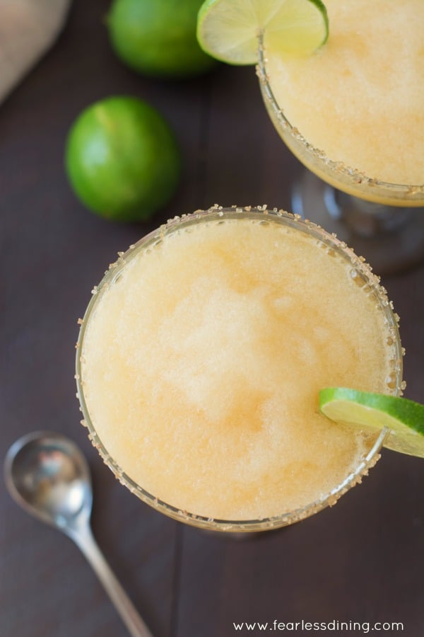 Top view of a glass of frozen peach margarita with fresh limes