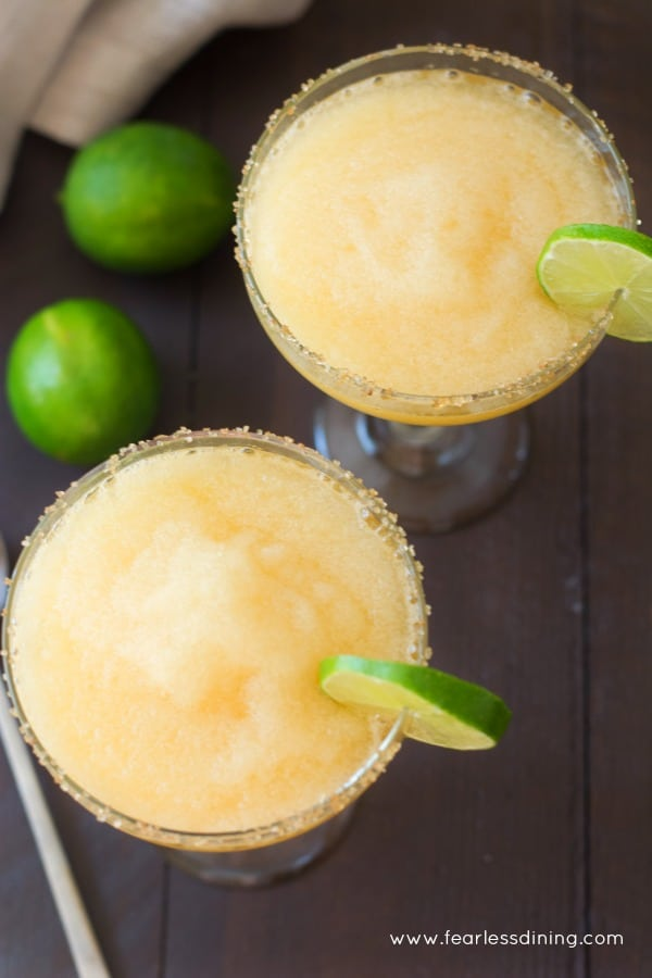 Top view of two glasses of frozen peach margaritas
