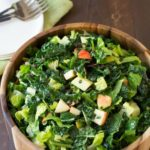 kale salad with apples in a wooden salad bowl
