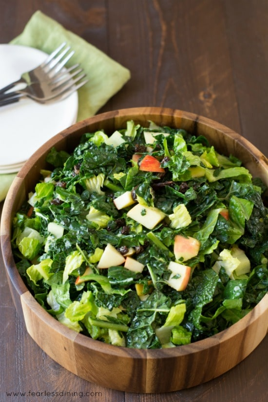healthy kale salad with apples and raisins in a large wooden bowl. Plates and forks are behind the bowl