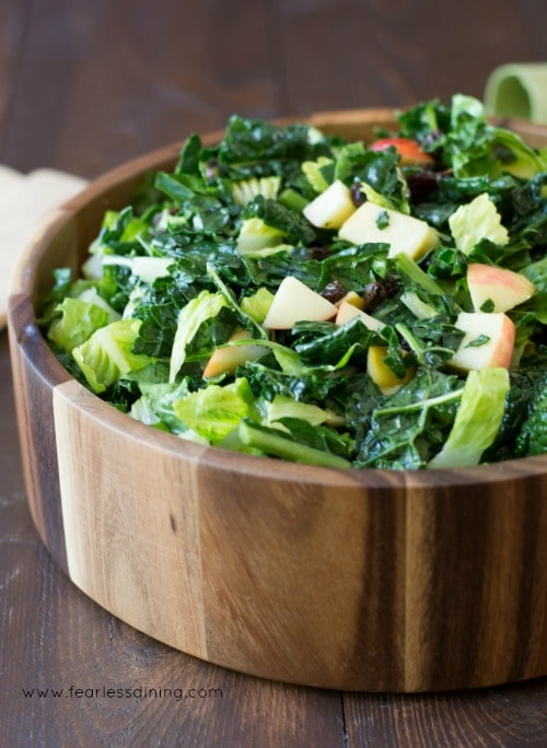 Close up image of kale and apple salad in a wooden bowl