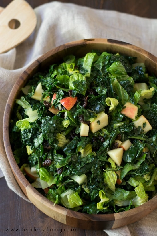Top view of Kale and Apple Salad in a wooden bowl