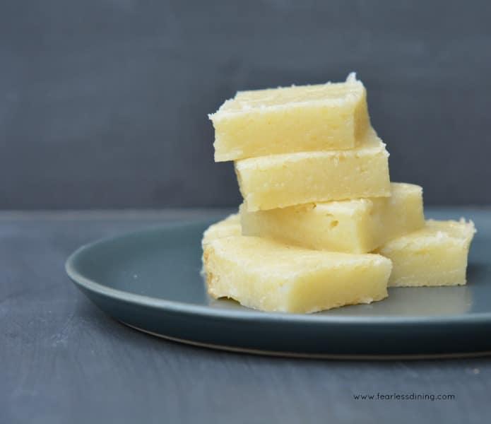 Hawaiian Bata - Hawaiian Butter Mochi squares stacked on a grey plate.