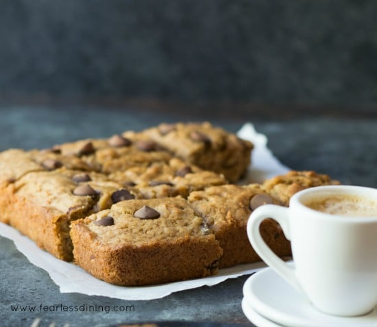 gluten free banana bars on a piece of parchment paper next to a cup of espresso.