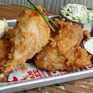 gluten free fried chicken on a plate, garnished with chives