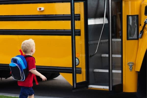 back view of a child getting onto a school bus