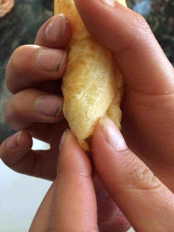 Pinching the bottom of a homemade gluten free waffle cone closed