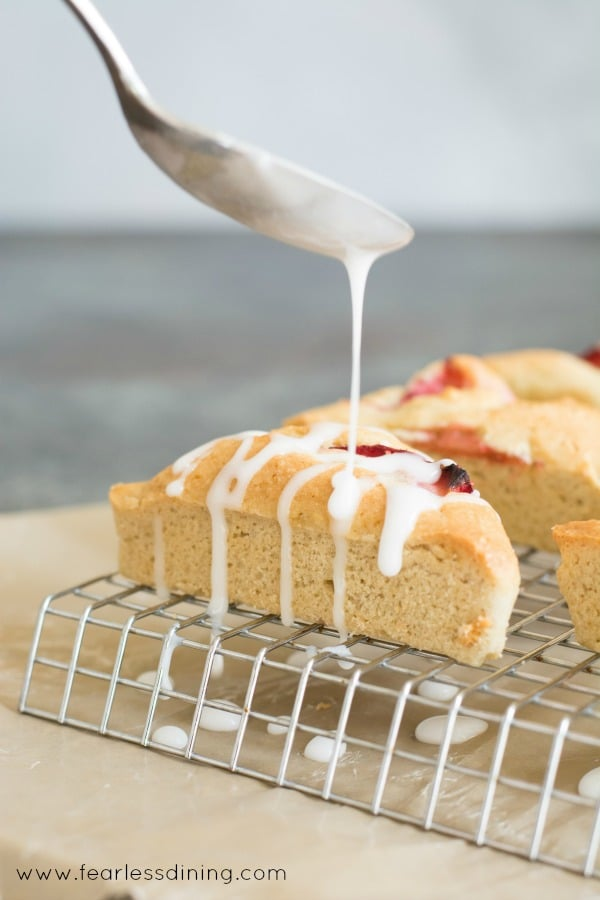 Gluten free strawberry scones with creamy icing being drizzled on top.