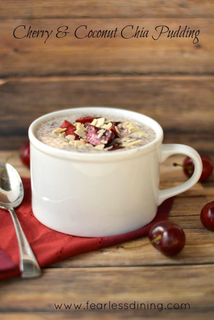 Cherry and Coconut Chia Pudding in a mug. The chia pudding has fresh cherries and almonds on top
