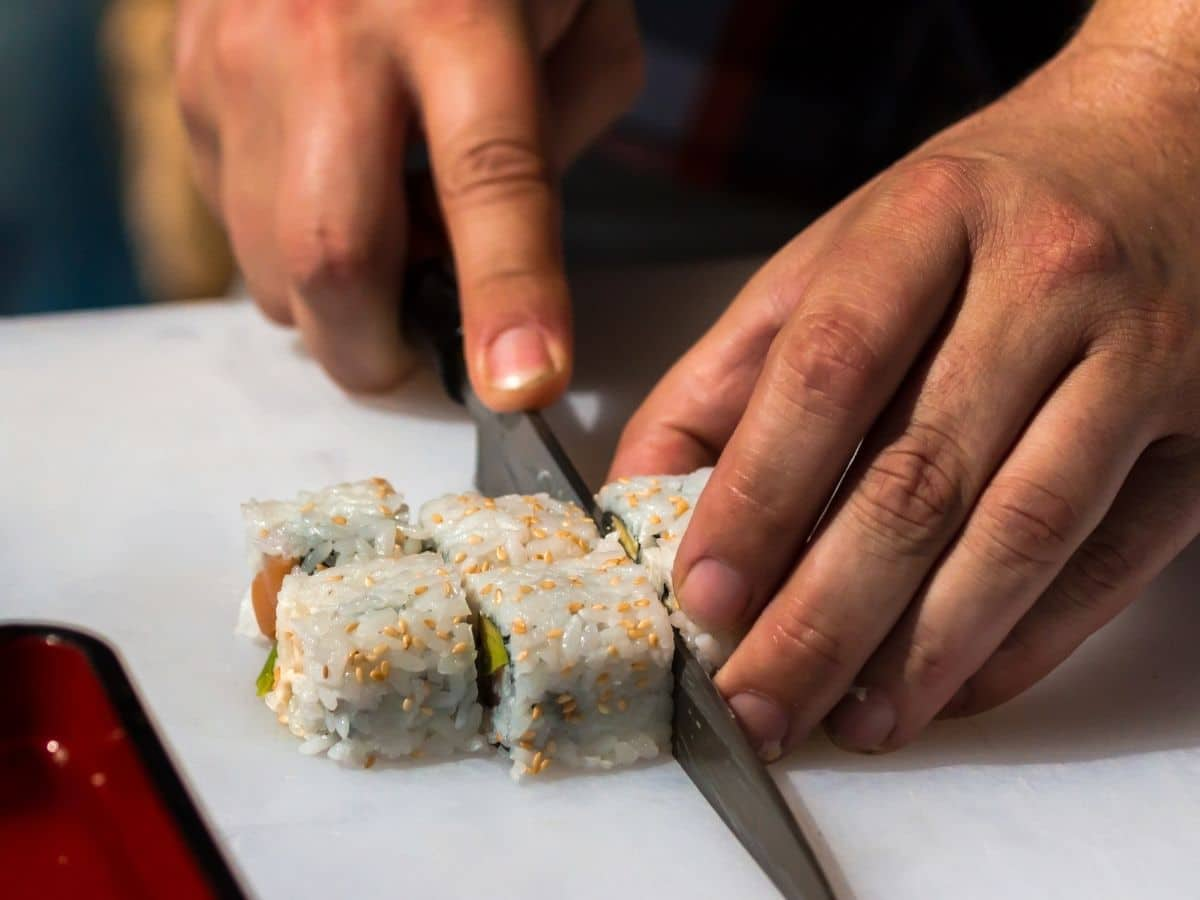 cutting a sushi roll with a large knife