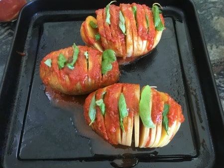 Hassleback potatoes with pizza sauce and basil in the layers