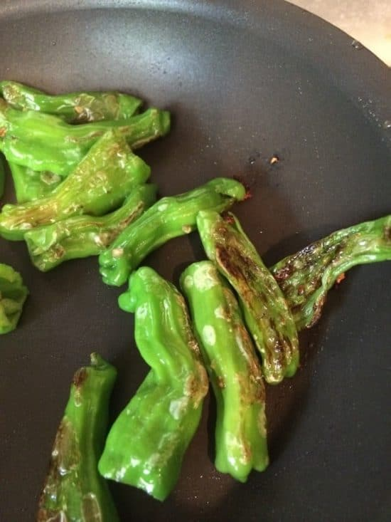Charring shishito peppers in a frying pan.