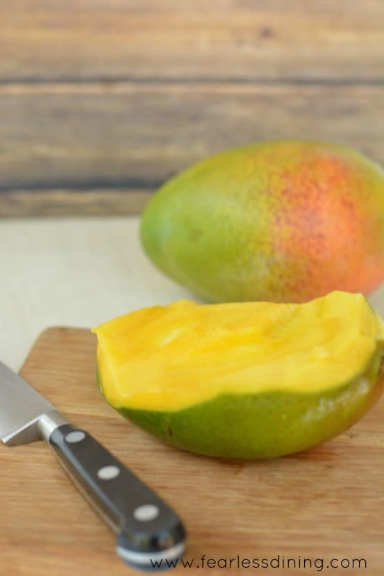 Fresh mango on a cutting board with a knife