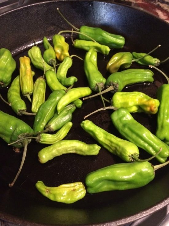 shishito peppers roasting in a cast iron skillet