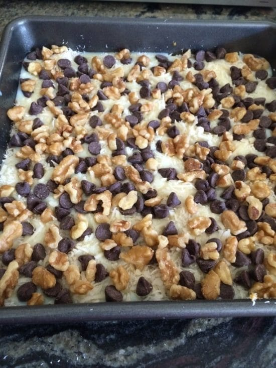 Adding walnuts and chips to the magic bars