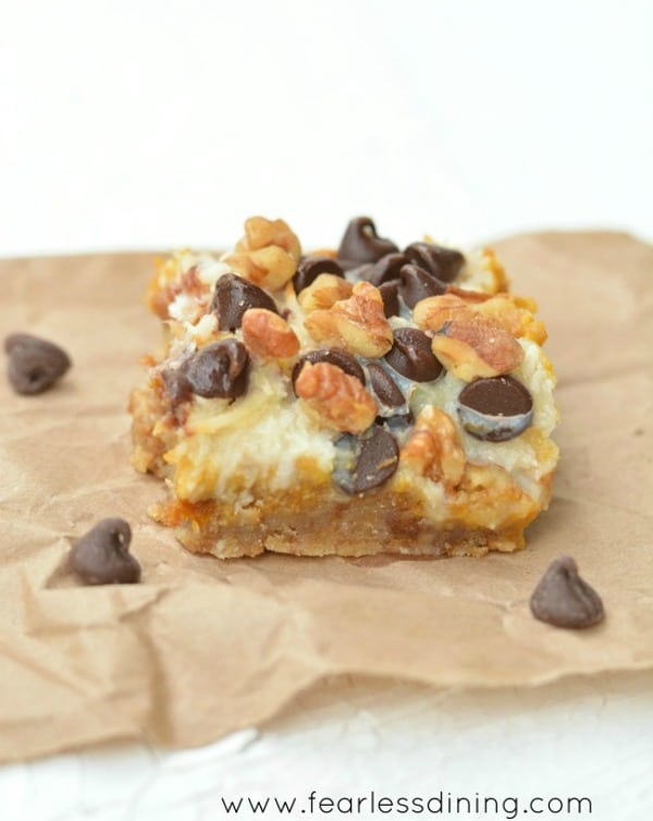 a close up of a gluten free pumpkin 7 layer bar on a brown napkin