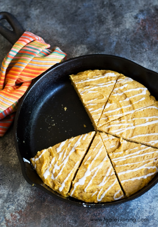 A cast iron skillet with slices of a giant pumpkin cookie cut out