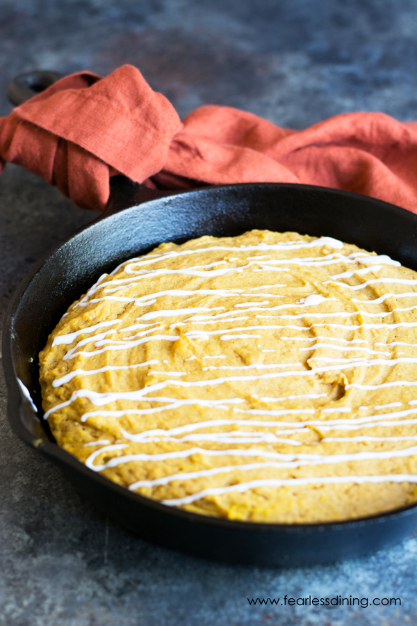 A cast iron skillet with a giant pumpkin cookie baked in it. White icing is drizzled on top