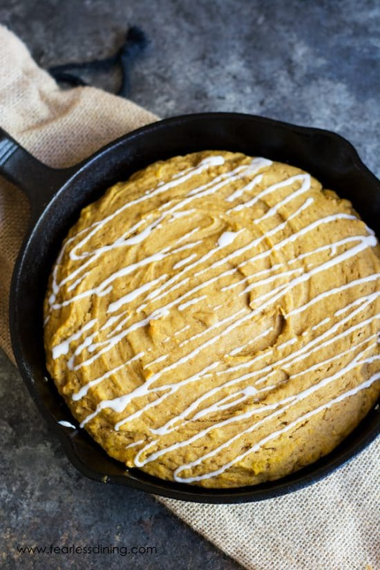 A cast iron skillet filled with a giant gluten free pumpkin cookie