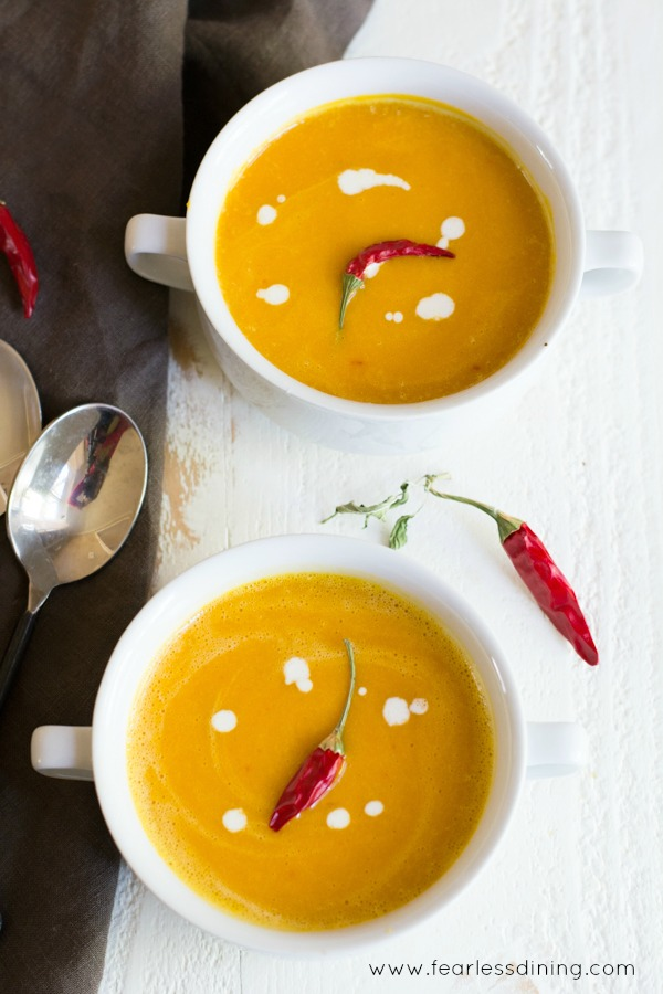 Two white bowls of kuri squash soup. They are garnished with coconut milk and red Thai chili peppers