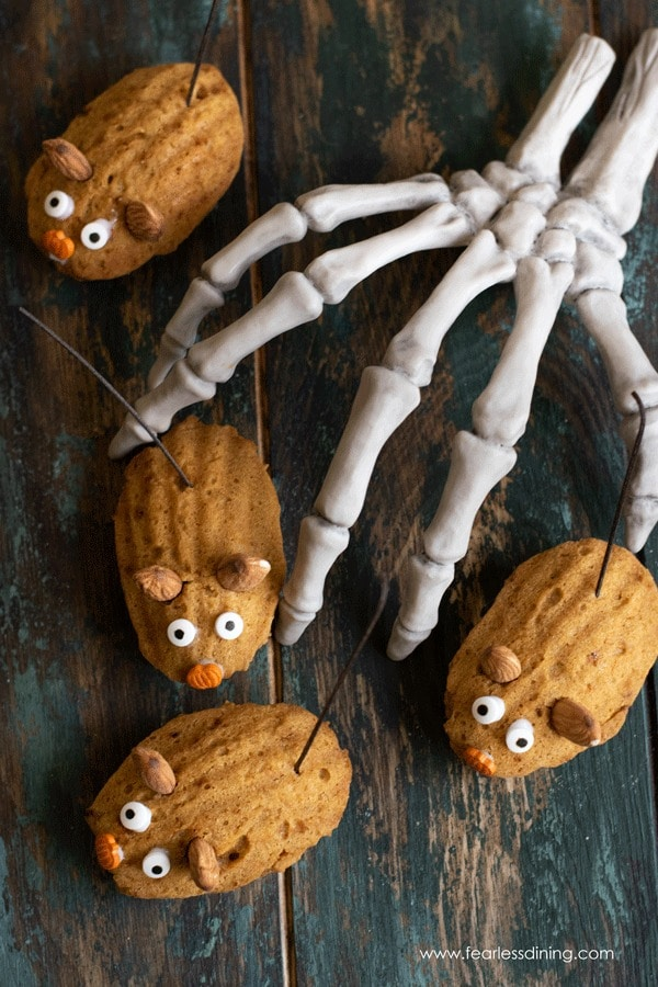 Gluten free pumpkin madeleines decorated like mice with a skelatel hand