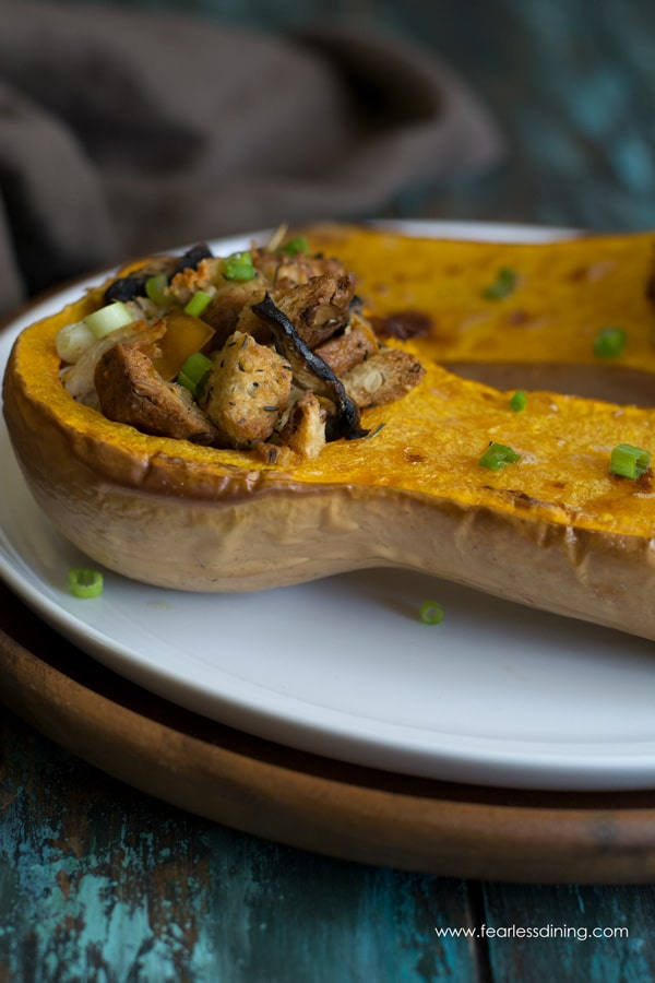 Side view of a half of roasted butternut squash filled with stuffing and turkey
