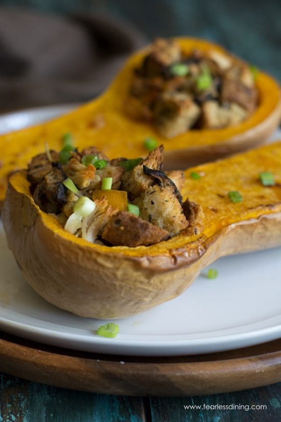 Two halves of stuffed butternut squash on a plate