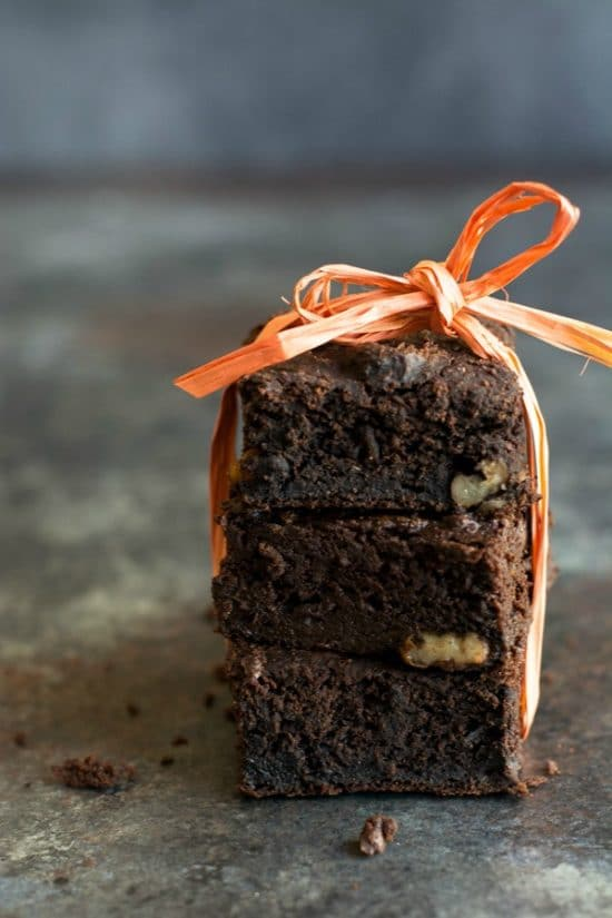 A Stack of three paleo chocolate brownies. An orange piece of rafia is tied around the brownies in a bow