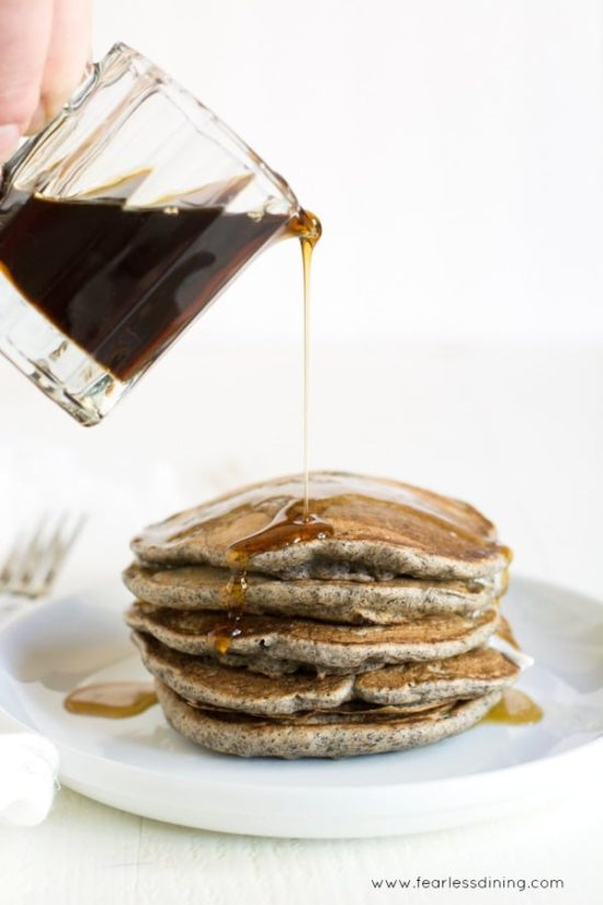 maple syrup being poured onto a stack of gluten free buckwheat pancakes