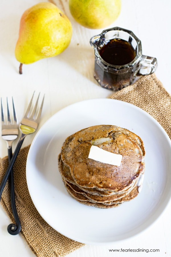 The top view of a stack of buckwheat flour pancakes on a plate. Forks and syrup are next to the plate.