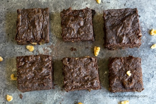 The top view of six coconut flour brownies lined up. on a counter top