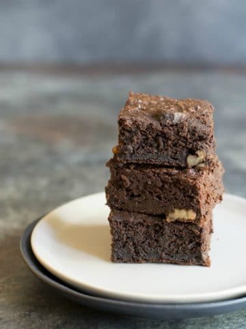 stack of coconut flour brownies on a white plate