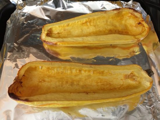 roasted delicata squash sliced in half vertically on a foil lined baking tray