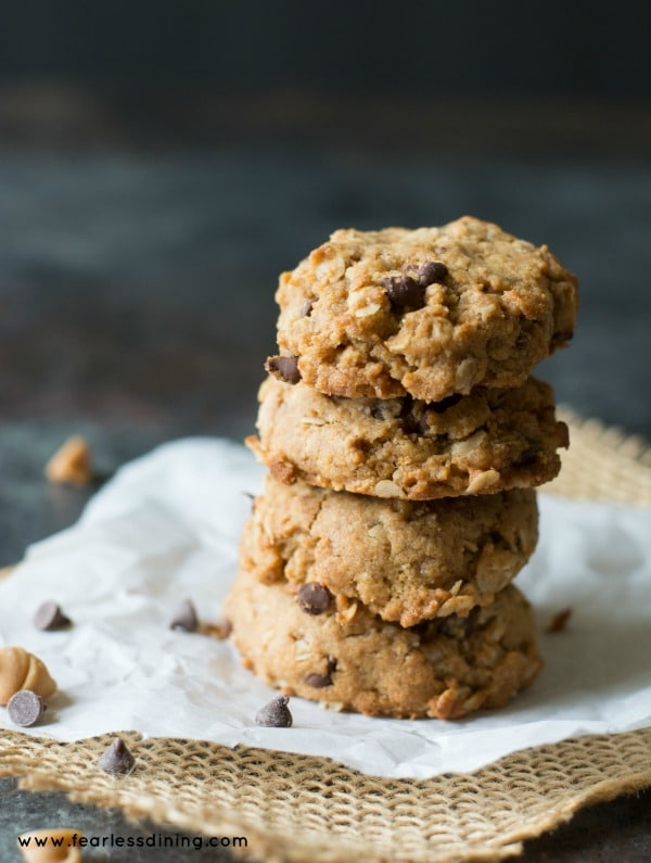 Four Gluten Free Peanut Butter Oat Triple Chip Cookies stacked on top of each other with chocolate chips on the table