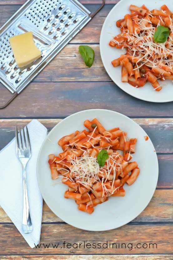 Gluten free al dente pasta with marinara sauce served on plates. A piece of cheese is sitting on a cheese grater next to the plates