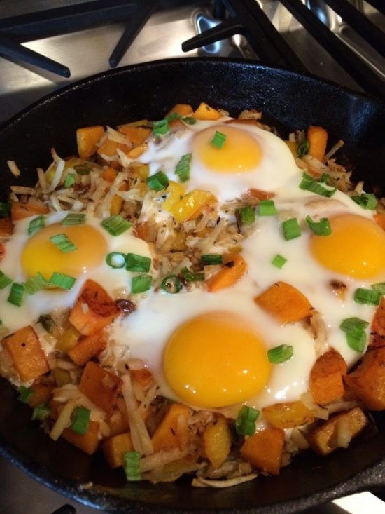 broiling eggs over vegetables in a cast iron skillet
