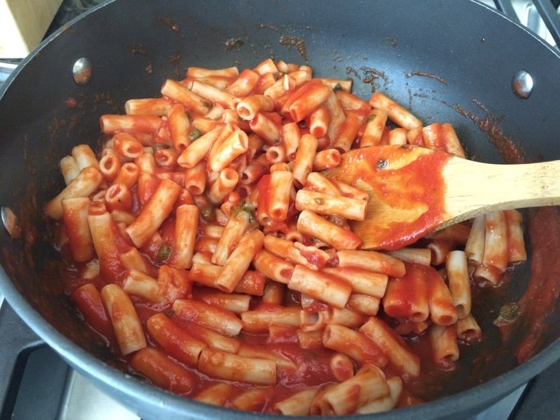 Tomato garlic and basil sauce mixing into pasta with a wooden spoon.