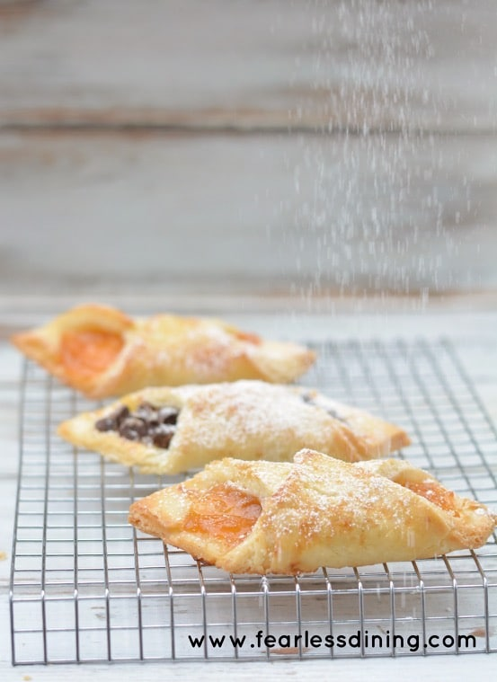 Sprinkling powdered sugar onto Flaky Gluten Free Pastries