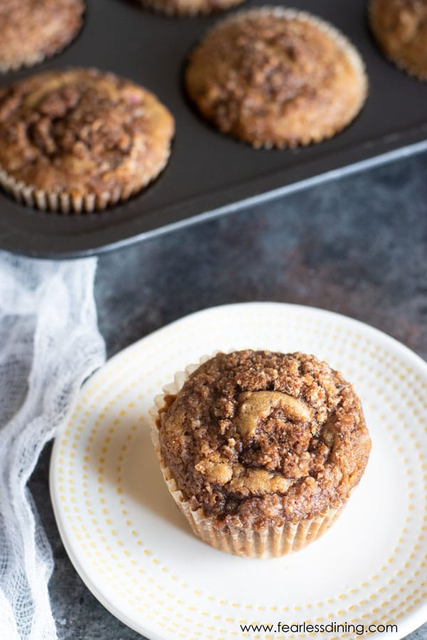 a gluten free cinnamon streusel muffin on plate with the muffin tin in the background