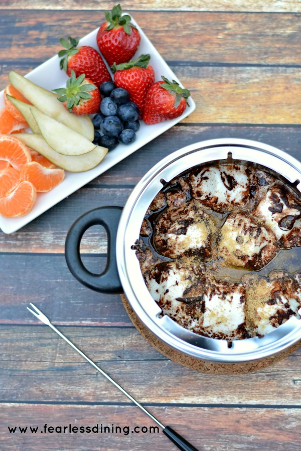 Gluten Free S'mores Chocolate Fondue in a fondue pot with a plate of fresh cut fruits