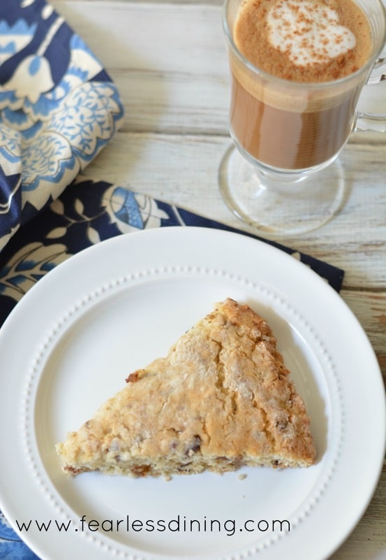 Gluten Free Coconut, Date, and Pecan Scone wedge on a plate. The plate is on a navy colored floral napkin.
