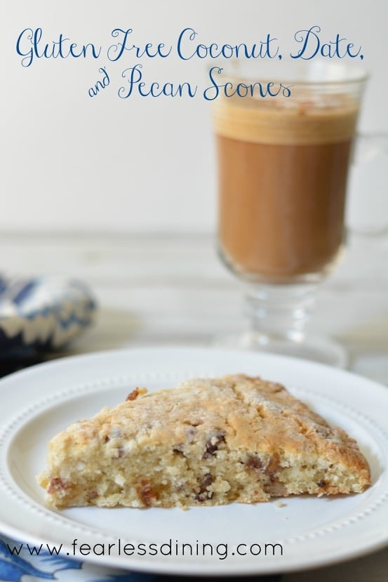 Gluten Free Coconut, Date, and Pecan Scone on a plate. A glass mug of coffee is in the background