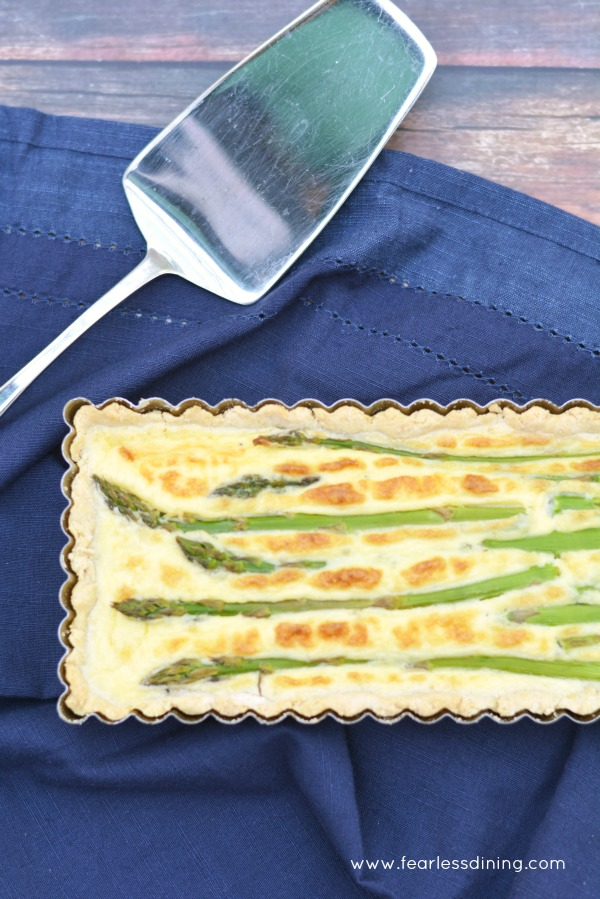 A Gluten Free Asparagus Goat Cheese Tart with a serving spoon on the side.