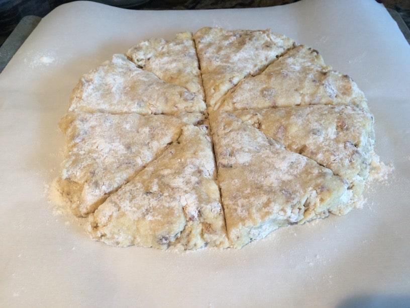 date scone dough pressed into a circle. Cuts are made to make triangle scones